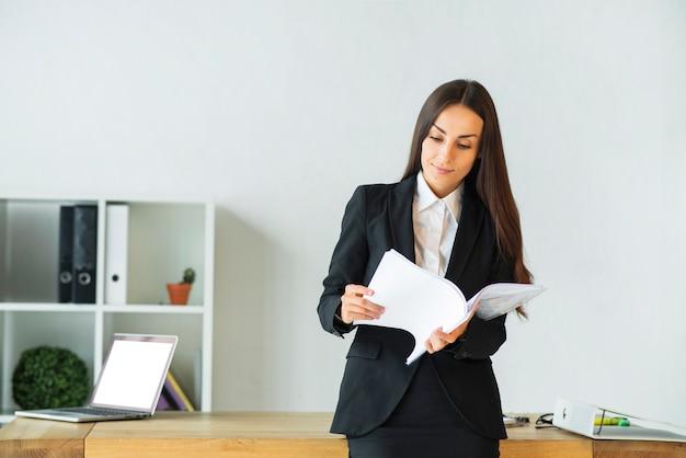 Jovem, executiva, ficar, frente, escrivaninha escritório, leitura, documentos