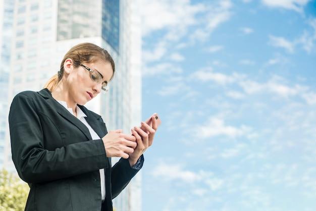 Jovem, executiva, ficar, frente, predios, texting, mensagem, ligado, telefone móvel