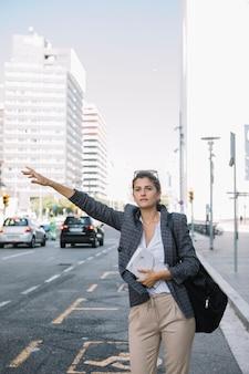 Jovem, executiva, saudando, táxi, ligado, rua cidade
