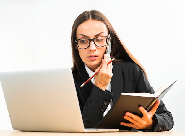 Jovem, executiva, segurando, diário, em, mão, olhar, laptop, enquanto, falando, ligado, smartphone