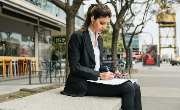 Jovem, executiva, sentando, ligado, banco, escrita, ligado, papel, segurando, telefone móvel, em, mão