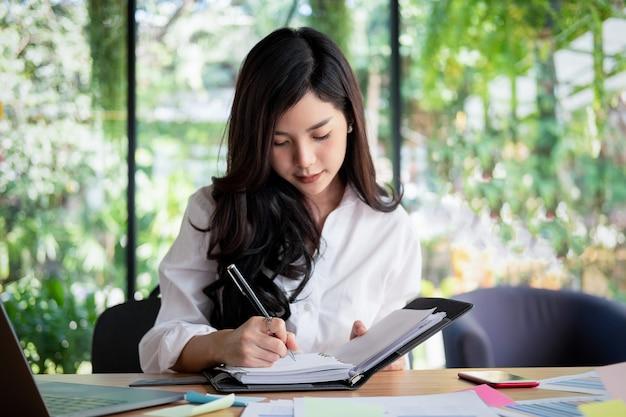 Jovem, executiva, trabalhando, com, laptop, documentos, em, escritório, conceito negócio