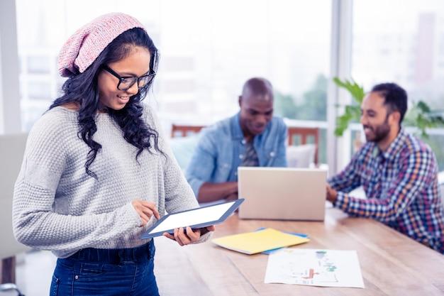 Jovem, executiva, usando, tablete digital, enquanto, ficar, em, escritório