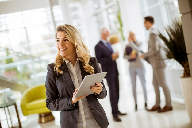 Jovem, executiva, usando, tabuleta, em, escritório, enquanto, outro, pessoas negócio, falando, em, fundo