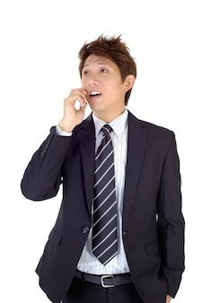 Jovem executivo animado usando o celular, closeup retrato na parede branca.