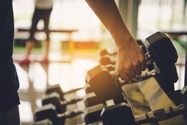 Jovem exercita em uma academia profissional com uma seleção de equipamentos de ginástica