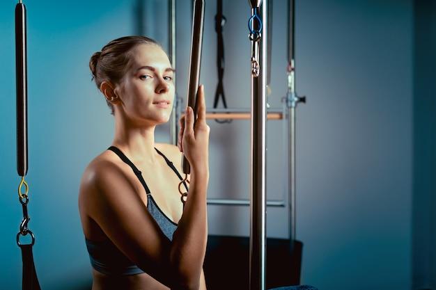 Jovem exercita sobre uma cama de reformadores de pilates, no corredor em um fundo de uma parede cinza.