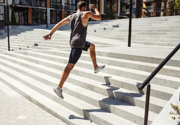 Jovem exercitando fora. vista lateral traseira do cara forte e rápido pulando vários degraus do lado de fora na rua. atletista poderoso treinando ou tendo treino. crescendo com força corporal.