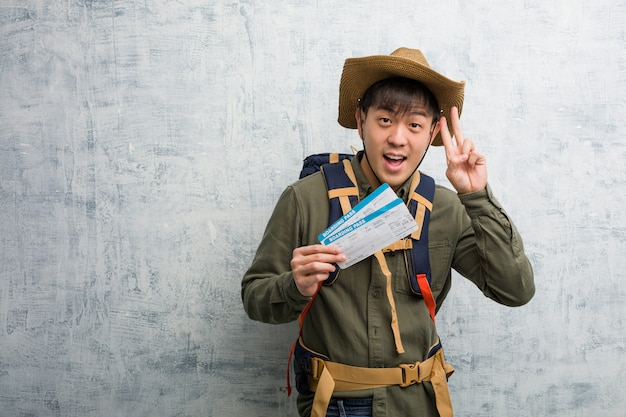 Jovem explorador chinês homem segurando uma divertida de bilhetes de ar e feliz fazendo um gesto de vitória