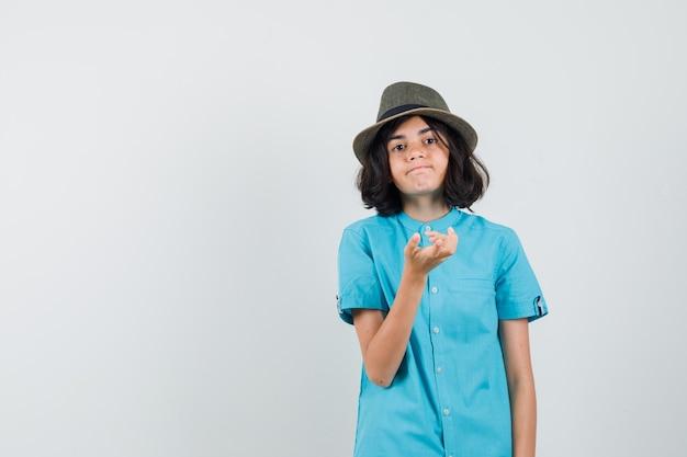 Jovem, expressando seus sentimentos com a mão na camisa azul, chapéu e parecendo emocional.