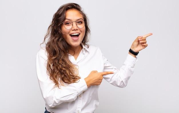 Jovem expressiva com óculos e blusa branca elegante posando na parede branca