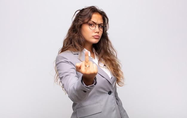Jovem expressiva com óculos e elegante terno posando na parede branca