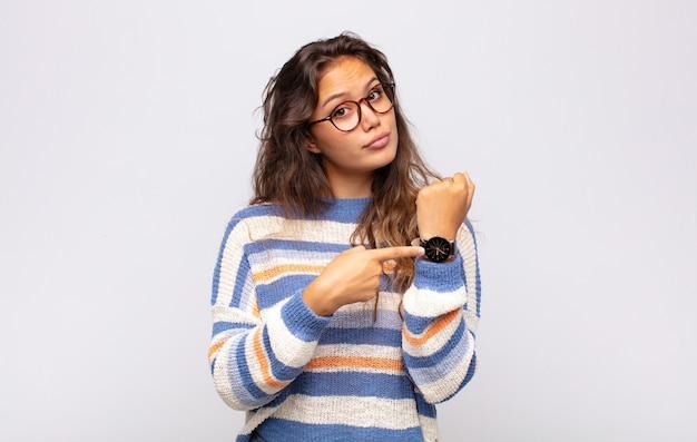 Jovem expressiva com óculos posando na parede branca