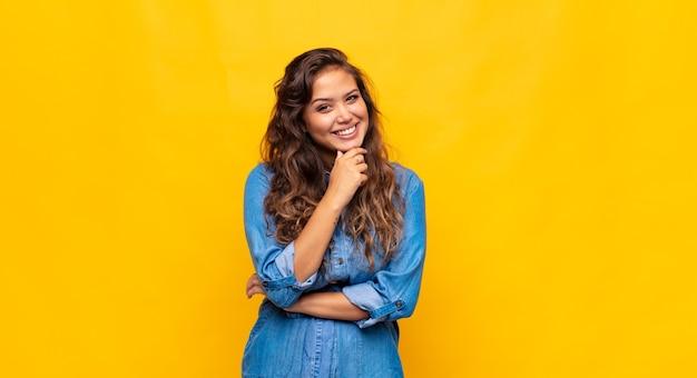 Jovem expressiva posando na parede amarela
