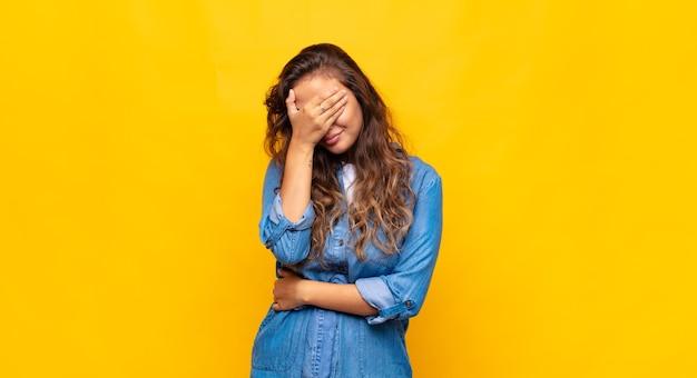 Jovem expressiva posando na parede amarela Foto Premium