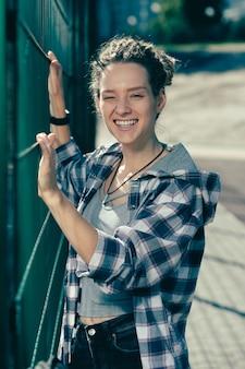 Jovem expressiva sorrindo alegremente e piscando em pé perto da cerca de arame do campo de esportes
