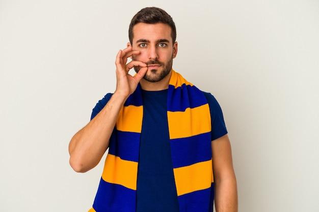 Jovem fã caucasiano de um time de futebol isolado no fundo branco com os dedos nos lábios, mantendo um segredo.