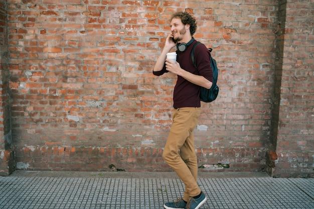Jovem, falando ao telefone ao ar livre.