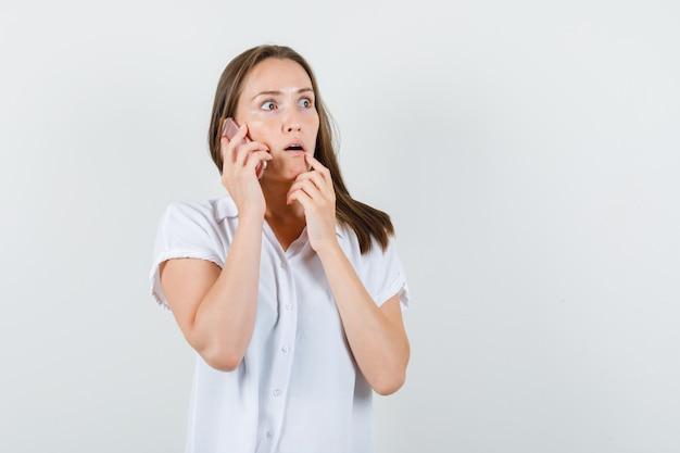 Jovem falando ao telefone de blusa branca e parecendo preocupada