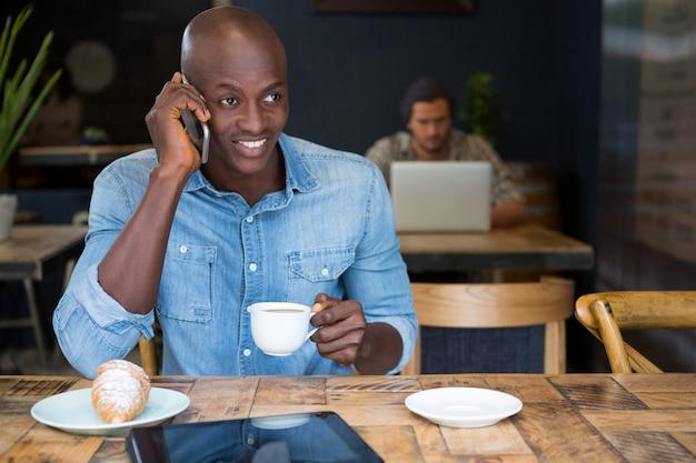 Jovem falando ao telefone enquanto toma um café na mesa da cafeteria