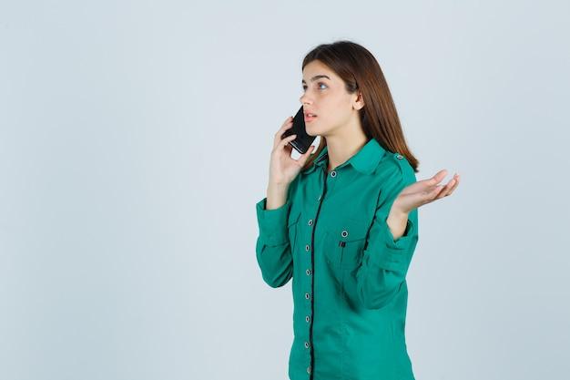 Jovem falando ao telefone, espalhando as palmas das mãos em uma blusa verde, calça preta e olhando com foco, vista frontal.