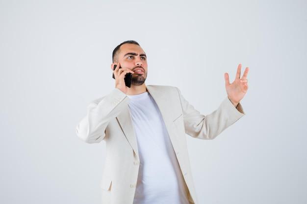 Jovem falando com alguém através do telefone, em t-shirt branca, jaqueta e olhando sério, vista frontal.