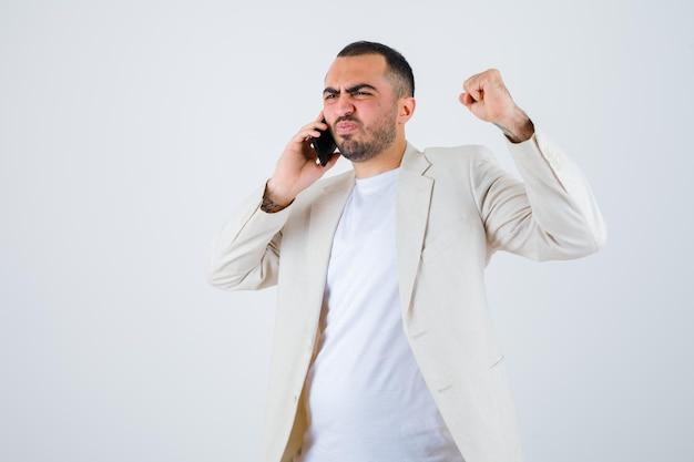 Jovem falando com alguém via telefone, cerrando o punho em camiseta branca, jaqueta e parecendo furioso, vista frontal.