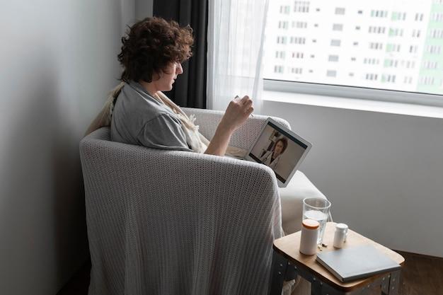 Jovem falando com seu médico por videochamada
