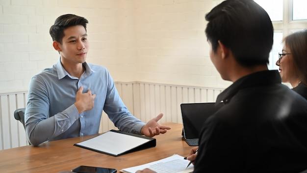 Jovem falando com trabalho de entrevista no escritório moderno.