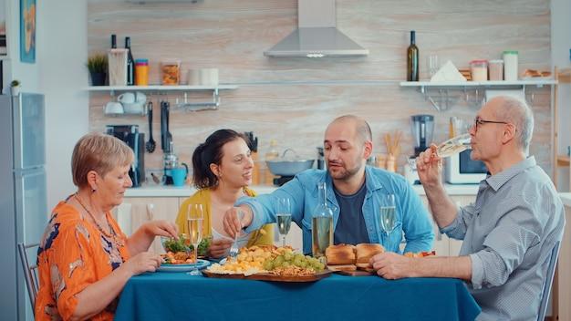 Jovem falando durante o jantar multi geração, quatro pessoas, dois casais felizes discutindo e comendo durante uma refeição gourmet, curtindo o tempo em casa, na cozinha sentado à mesa.
