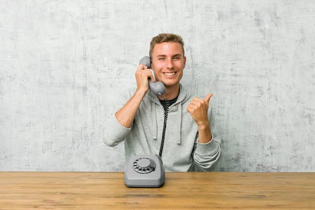 Jovem, falando em um telefone vintage, levantando os dois polegares, sorrindo e confiante.