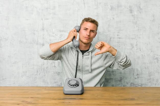 Jovem, falando em um telefone vintage, mostrando o polegar para baixo e expressando antipatia.
