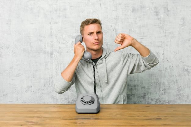 Jovem, falando em um telefone vintage, mostrando um gesto de antipatia, polegares para baixo. conceito de desacordo.
