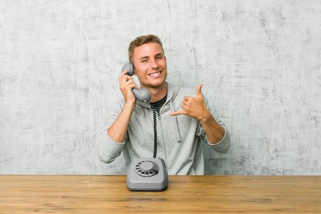 Jovem, falando em um telefone vintage, mostrando um gesto de chamada de telefone móvel com os dedos.
