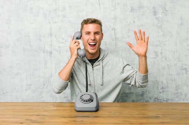 Jovem, falando em um telefone vintage, recebendo uma agradável surpresa, animado e levantando as mãos.