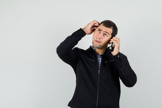 Jovem falando no celular, coçando a cabeça na camisa, jaqueta e olhando pensativo. vista frontal.
