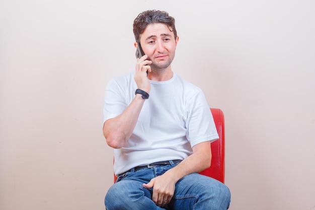 Jovem falando no celular enquanto está sentado na cadeira, de camiseta, jeans