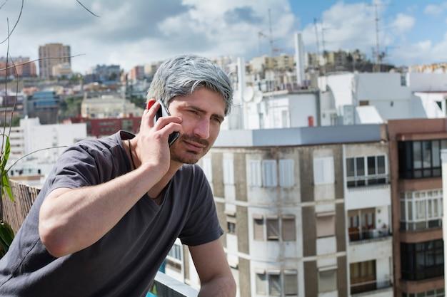 Jovem falando no seu smartphone, apoiando-se no terraço