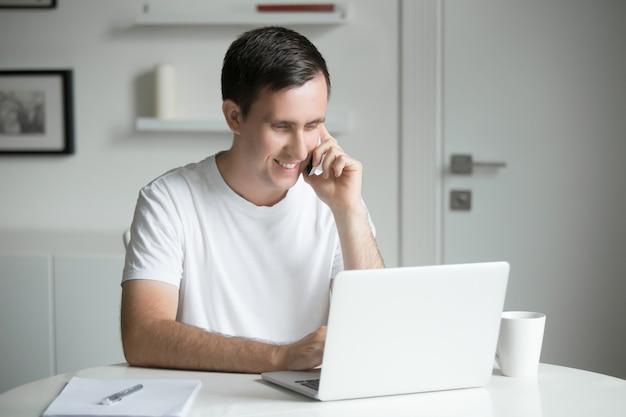 Jovem falando no telefone na mesa branca trabalhando no laptop