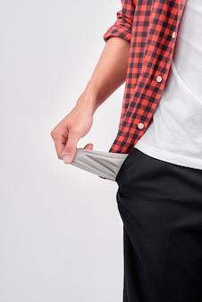 Jovem falido mostrando os bolsos vazios