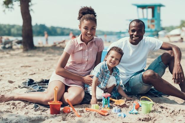 Jovem família afro-americana está sentada na praia de areia do rio.