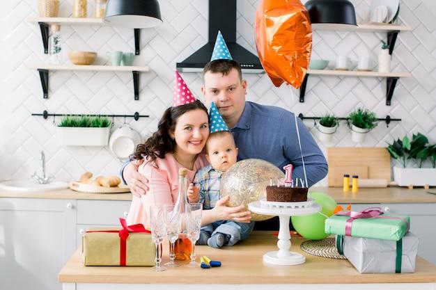 Jovem família caucasiana feliz comemorando uma primeira festa de aniversário de seu bebê