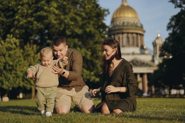 Jovem família caucasiana, pai, mãe e filho, sentado na grama em frente ao gato de são isaac