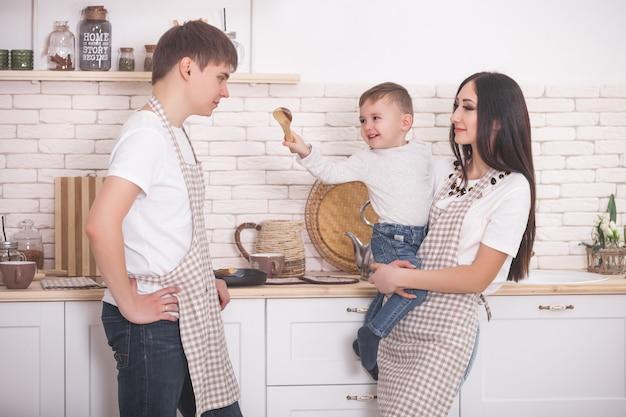 Jovem família cozinhando juntos. marido, esposa e seu bebê na cozinha. família amassar a massa com farinha. as pessoas cozinham o jantar ou café da manhã.