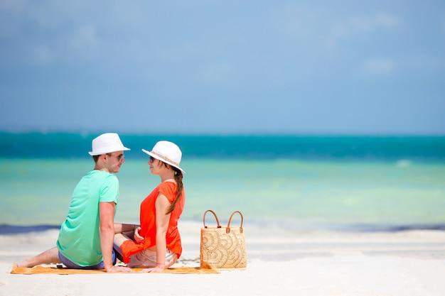Jovem família de dois na praia branca durante as férias de verão