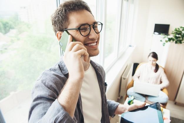 Jovem família de negócios, caucasiana, trabalhando na sala de estar perto da janela no laptop enquanto fala ao telefone