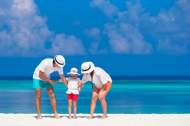 Jovem família de três na praia branca durante férias tropicais