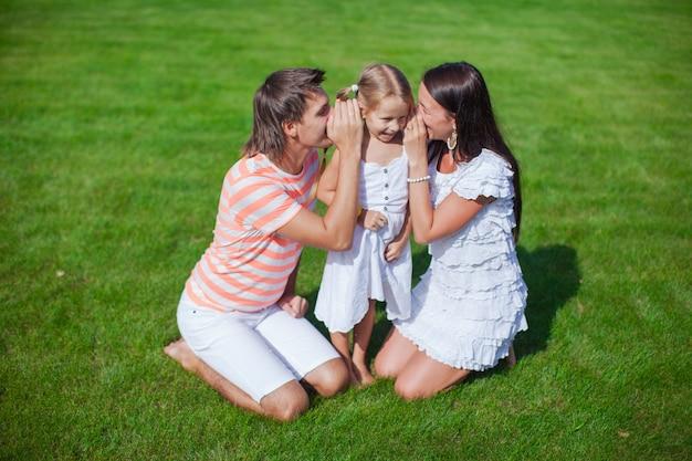 Jovem família de três sentados na grama e se divertir