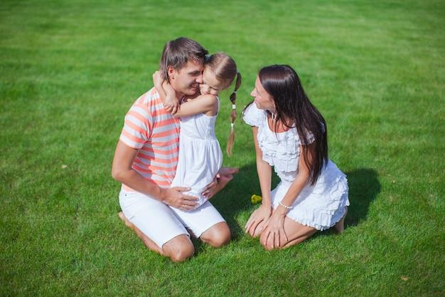 Jovem família de três sentar na grama e se divertir