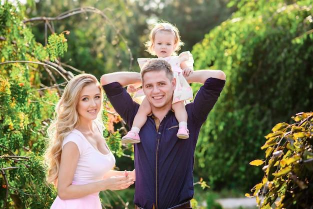 Jovem família feliz com bebê lindo de olhos azuis, caminhando no parque de verão ao pôr do sol